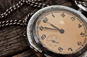 Old pocket watch on a rustic vintage wooden background
