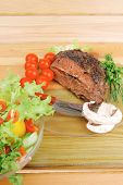 beef on transparent plate with salad bowl