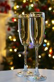 Two champagne glasses on table, on fir-tree background