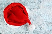 Santa red hat with snowflakes on color wooden background