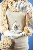 Christmas decoration in female hands on color background