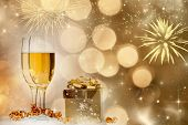 Glasses with champagne and gift box against fireworks and holiday lights