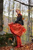 Beautiful elegant blonde woman in autumn forest