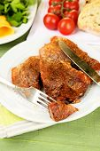Roasted meat and vegetables on plate, on color wooden table background