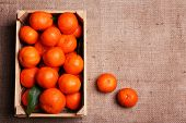 Fresh ripe mandarins in wooden box, on sackcloth background