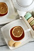 Colorful macaroons with teapot and cup of tea on color wooden  background