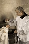 Sepia image of a vintage priest baptizing a baby