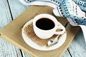 Cup of coffee on book with tablecloth on color wooden background