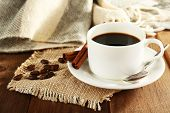 Cup of coffee with coffee beans and cinnamon on burlap cloth on wooden table background