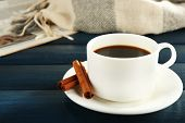 Cup of coffee with newspaper, plaid and cinnamon on color wooden background