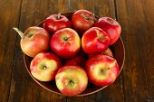 Bowl of red apples on wooden table background