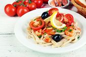 Tasty pasta with shrimps, black olives and tomato sauce on plate on wooden background
