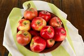 Bowl of red apples with napkin on wooden table background