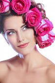 Portrait of a happy beautiful young woman with roses in her hair. Cosmetics. Beauty, fashion. Spring and summer. Copy space. Isolated over white background.