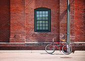 a bike in front of a brick wall during summer