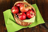 Wicker basket of red apples with green napkin on wooden background