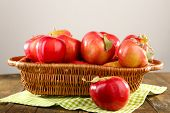 Wicker basket of red apples with napkin on wooden table, on light background