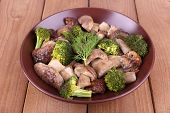 Braised wild mushrooms with vegetables and spices in plate on table