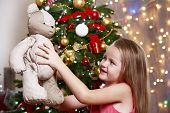 Little girl with teddy bear on bright background