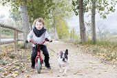 Child Riding Bike With Dog