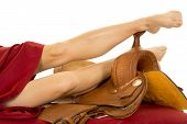 stock photo of western saddle  - a woman with her legs laying on top of a western saddle - JPG