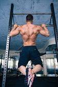 stock photo of pull up  - Back view portrait of a muscular handsome man pulling up at gym - JPG