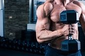 stock photo of dumbbell  - Closeup image of a muscular man workout with dumbbell - JPG