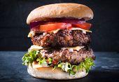 stock photo of beef-burger  - Big beef cheeseburger with vegetables - JPG