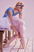 foto of ballet shoes  - Professional ballerina putting on her ballet shoes on the wooden floor on a pink background - JPG