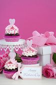 foto of cake stand  - Happy Mothers Day pink and white cupcakes on retro style cake stands and large gift box on vintage white wood table - JPG