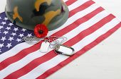 stock photo of memorial  - USA Memorial Day concept with dog tags and red remembrance poppy on American stars and stripes flag on white vintage wood table with copy space - JPG