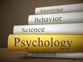 stock photo of psychological  - book title of psychology isolated on a wooden table over dark background - JPG