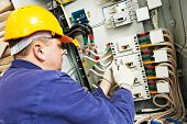 stock photo of assembly line  - electrician builder at work with tester measuring high voltage and current of power electric line in electical distribution fuseboard - JPG