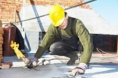 image of torches  - Roofer preparing part of bitumen roofing felt roll for melting by gas heater torch flame - JPG