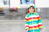 picture of rainy day  - Happy cute little child walking through rain in waterproof jacket - JPG