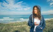 pic of hoodie  - Portrait of beautiful young woman with blue hoodie and sportswear holding her smartphone over a cloudy blue sky background - JPG