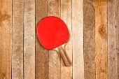 picture of ping pong  - Red ping pong paddle against wooden background - JPG