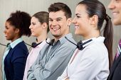picture of telemarketing  - Portrait of happy male call center employee standing in row with colleagues at office - JPG