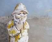 stock photo of gnome  - Old antique weathered garden gnome shallow DOF