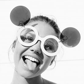 stock photo of tongue  - young girl in sunglasses showing tongue - JPG