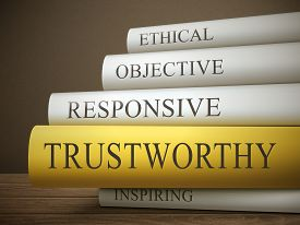 picture of trustworthiness  - book title of trustworthy isolated on a wooden table over dark background - JPG