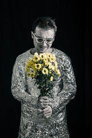 pic of spaceman  - Portrait of satisfied spaceman holding flowers - JPG