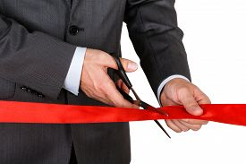 pic of pompous  - Businessman in suit cutting red ribbon with pair of scissors isolated on white background - JPG