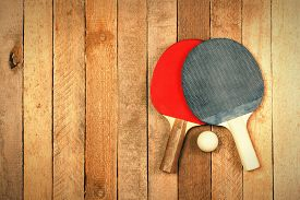 stock photo of ping pong  - Ping pong paddles and ball on wooden texture with copyspace - JPG