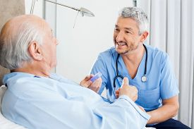 image of nursing  - Happy male caretaker discussing prescription medicine with senior man in bedroom at nursing home - JPG