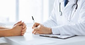 stock photo of hospital patient  - close up of patient and doctor taking notes - JPG
