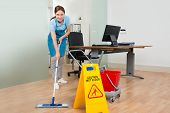 Female Janitor Cleaning Hardwood Floor In Office poster