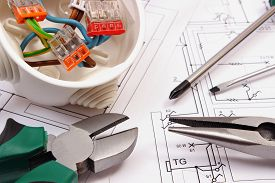 stock photo of electrical engineering  - Metal pliers screwdriver and cable connections in electrical box lying on electrical construction drawing of house work tool and drawing for engineer jobs concept of building house - JPG
