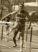 male runner competing during hurdles