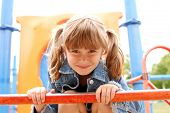 A cute young girl having fun on the jungle gym